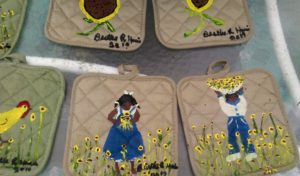 Various sunflower-themed painted potholders